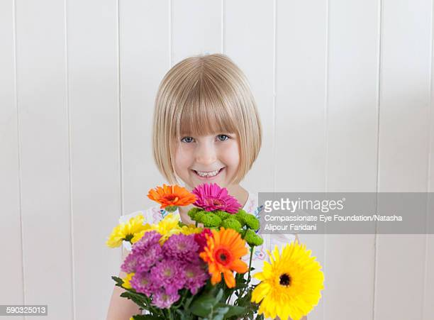 "girl holding bunch of flowers - ""compassionate eye"" stock pictures, royalty-free photos & images"