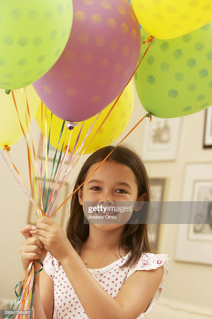 Girl (5-7) holding bunch of helium balloons, smiling, portrait : Stock Photo