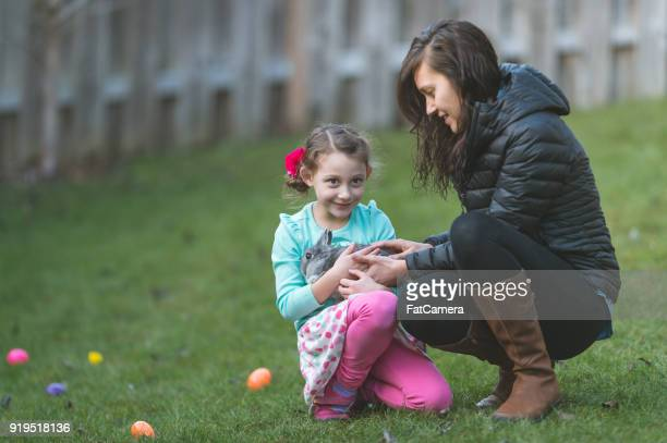 Girl holding bunny in backyard with her mother