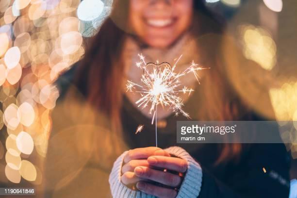 meisje houdt brandende sparkler tijdens kerstmis - verlangen stockfoto's en -beelden