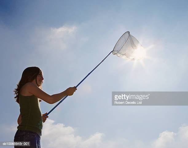Girl (11-12) holding butterfly net against sun, low angle view