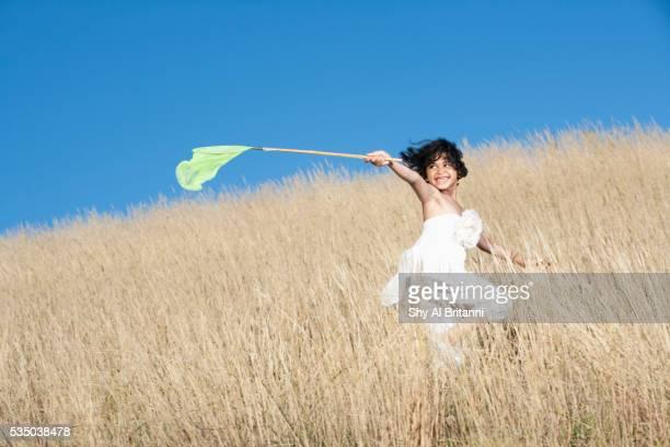 girl holding butterfly net in field - libre de droit photos et images de collection