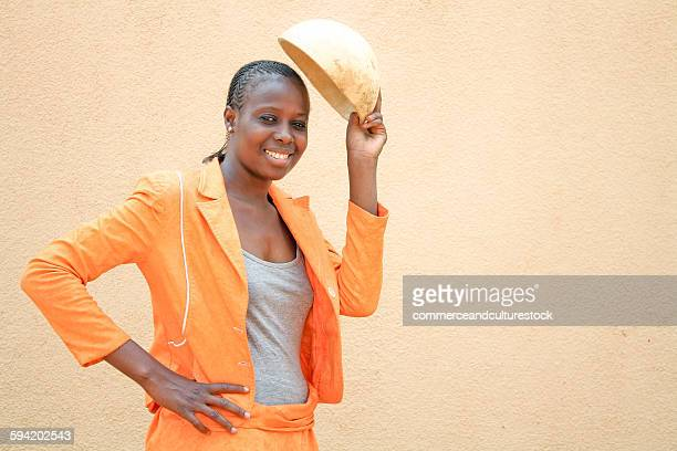A girl holding calabash as a helmet