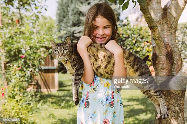 Girl holding cat in garden
