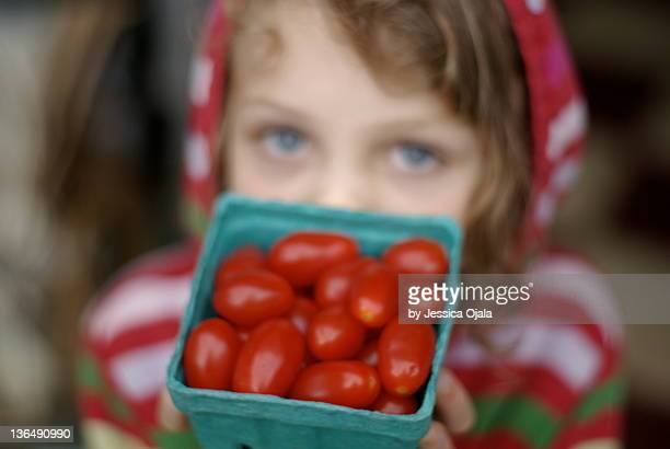 Girl holding cherry tomatoes