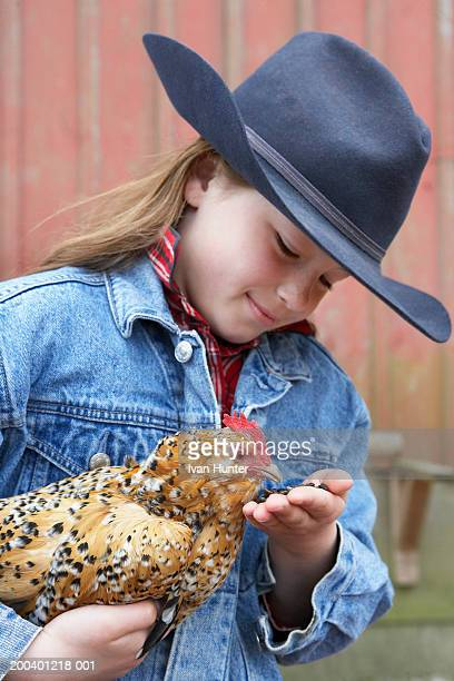 Girl (7-9) holding chicken, feeding out of hand