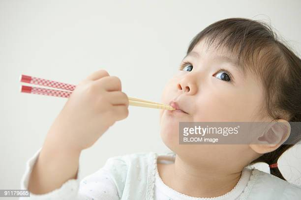 Girl holding chopsticks in mouth