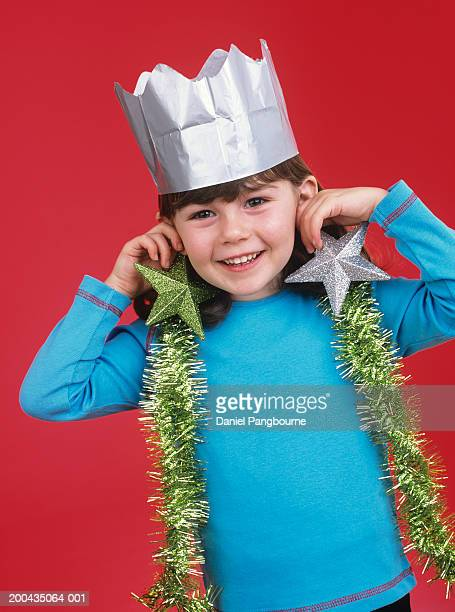 Girl (3-5) holding Christmas decorations up, smiling, portrait