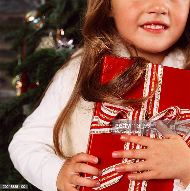 girl (2-4) holding christmas gift, close-up - microzoa stock pictures, royalty-free photos & images