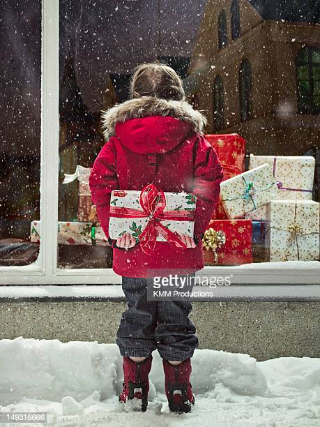 Girl holding Christmas present in snow