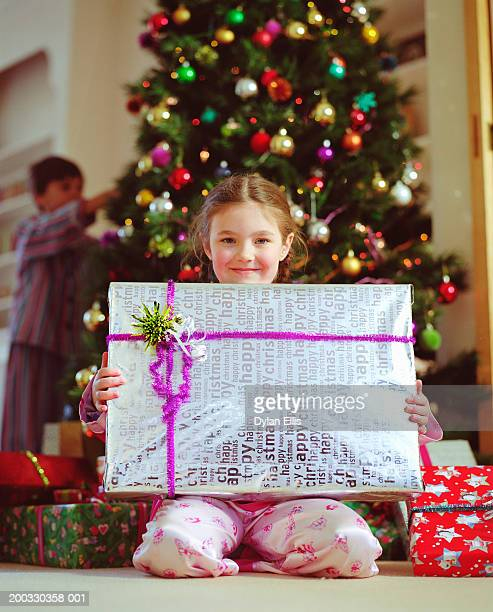 Girl (5-7) holding christmas present, smiling, portrait