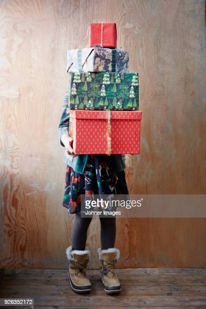 girl holding christmas presents - christmas gifts stock photos and pictures