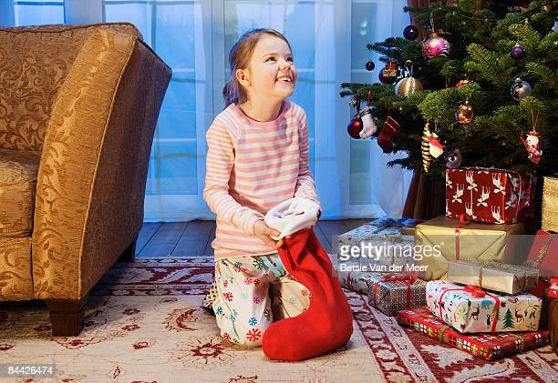 girl holding christmas stocking, laughing. - stockings photos stock pictures, royalty-free photos & images