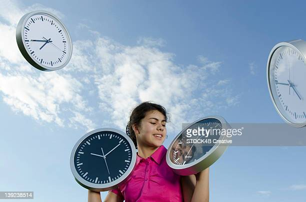 Girl holding clocks outdoors