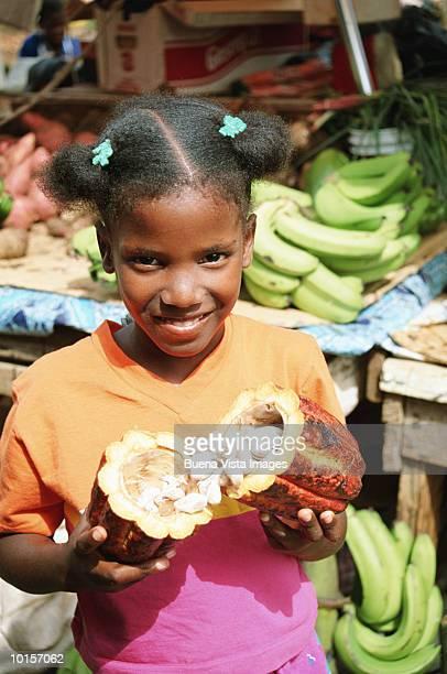 Girl (6-8) holding cocoa fruit in market, smiling, portrait