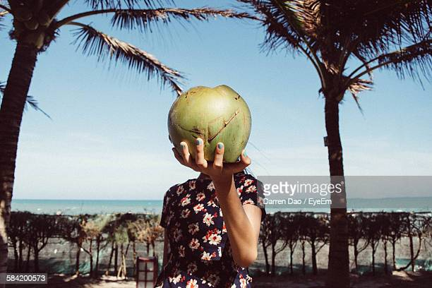 Girl Holding Coconut In Front Of Face At Beach