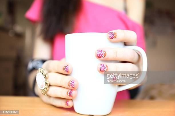 Girl holding coffee mug with cupcake nail design