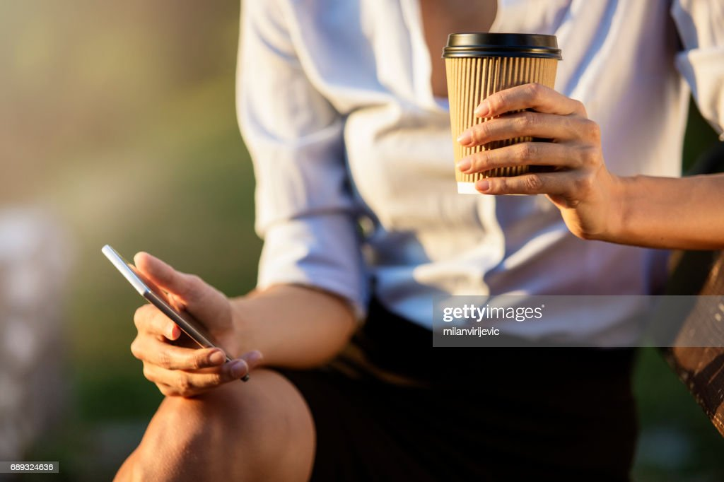 Girl holding coffee phone and texting : Stock Photo