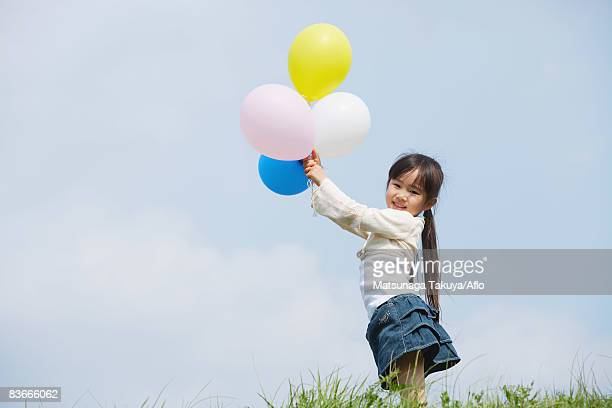 Girl holding colorful balloons against blue sky