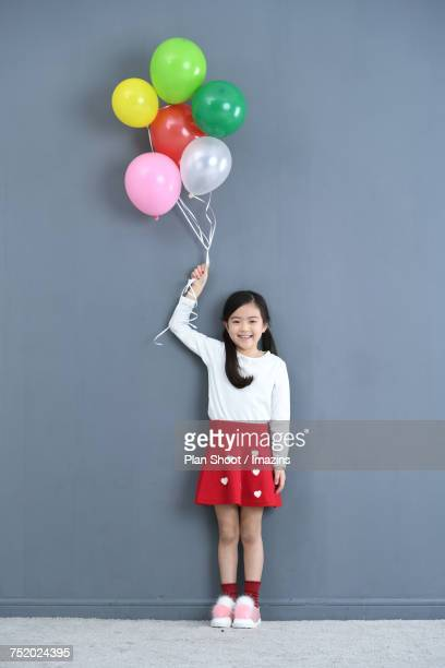 A girl holding colorful balloons