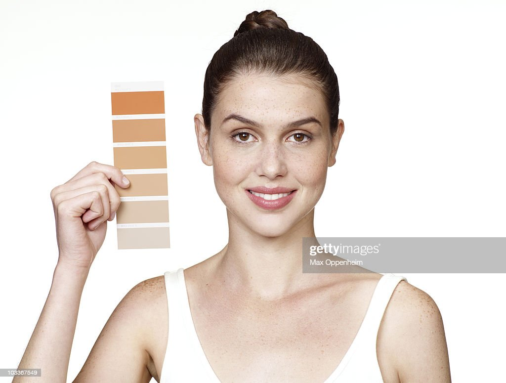 girl holding colour swatch to face : Stock Photo
