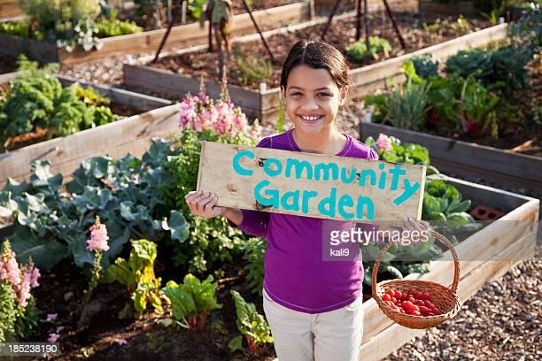 Girl holding community garden sign