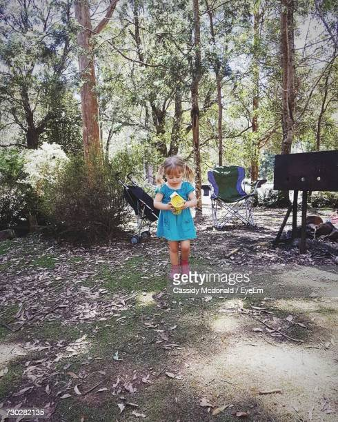 Girl Holding Container While Standing In Yard