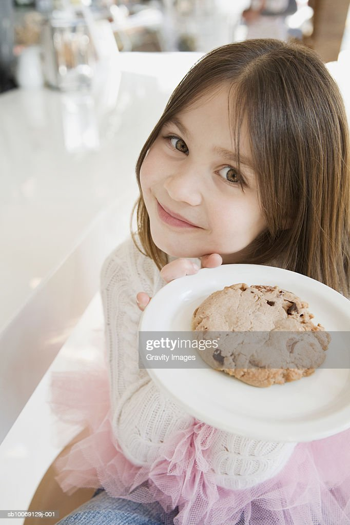 Girl (8-9) holding cookie in plate, smiling, portrait, high angle view : Stockfoto