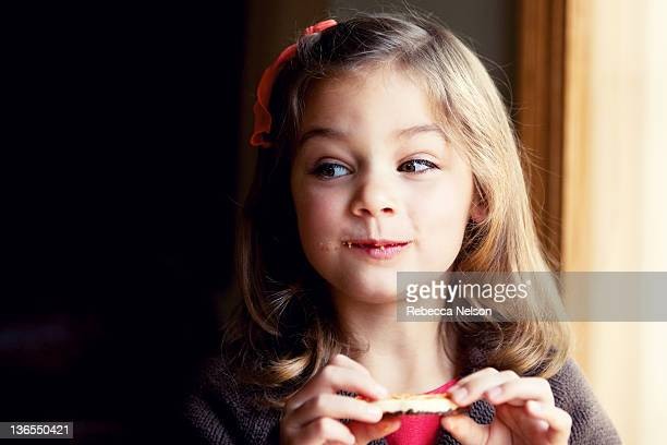 girl holding cookie with crumbs on her face - alleen één meisje stockfoto's en -beelden