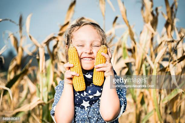 girl holding corn on the cob in field - alexandra dost stock-fotos und bilder