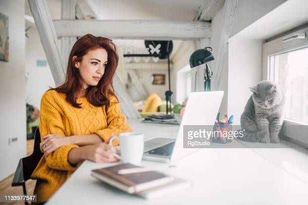 girl holding cup of coffee and looking at laptop - persian girl stock photos and pictures