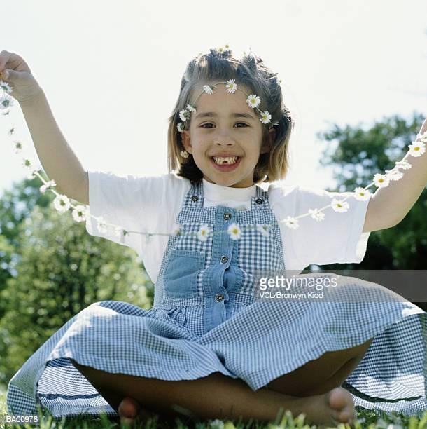 Girl (6-8) holding daisy chain, portrait