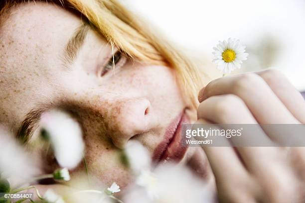 Girl holding daisy in her hand, close-up