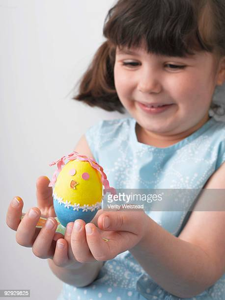 Girl holding decorated Easter egg