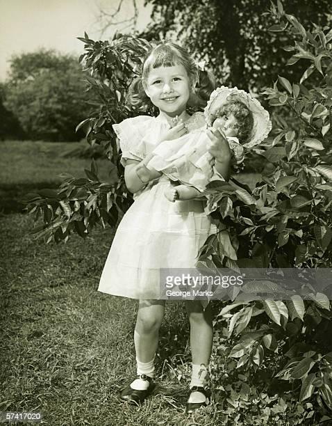 ragazza (6-7) con bambola in posa nel parco, (b & w), (verticale - solo una bambina femmina foto e immagini stock