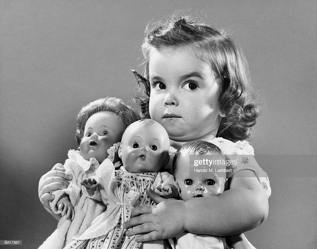 Girl (2-4) holding dollies, portrait (B&W) : Stock Photo