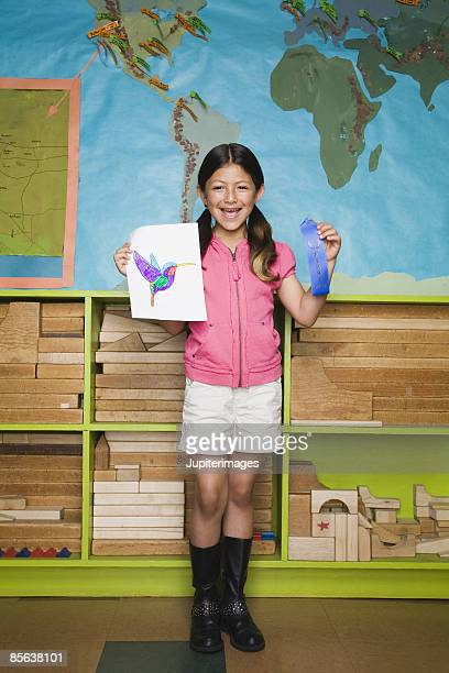 Girl holding drawing and award