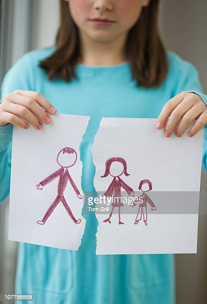 Girl holding drawing of split family