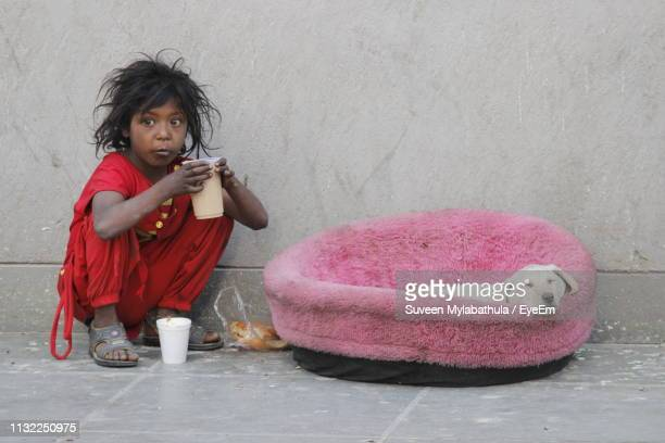 girl holding drink looking away while sitting with puppy on sidewalk - begging social issue imagens e fotografias de stock