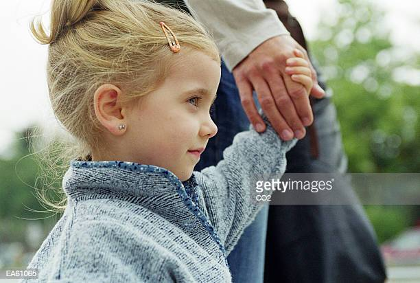 Girl (3-5) holding father's hand, close-up