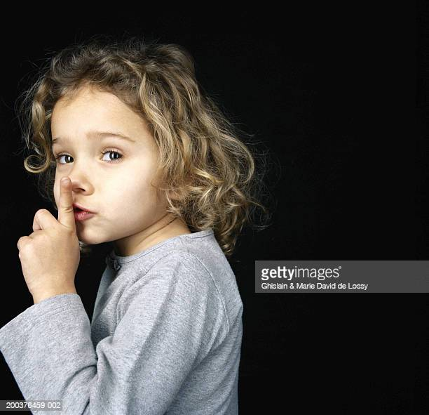 Girl (3-5) holding finger to lips, indicating 'quiet'