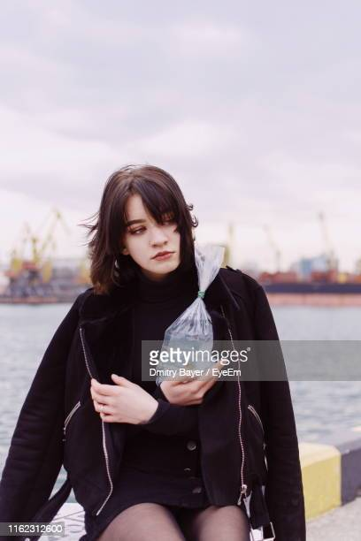 Girl Holding Fish In Plastic Bag While Sitting On Footpath Against Sea And Sky