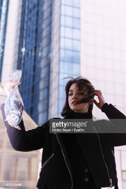 Girl Holding Fish In Plastic Bag While Standing Against Building