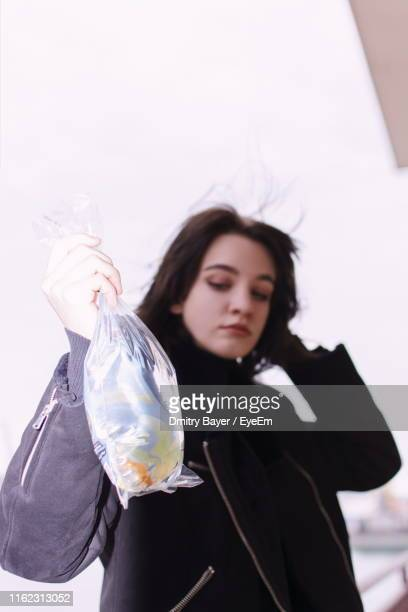 Girl Holding Fish In Plastic Bag While Standing Against Sky
