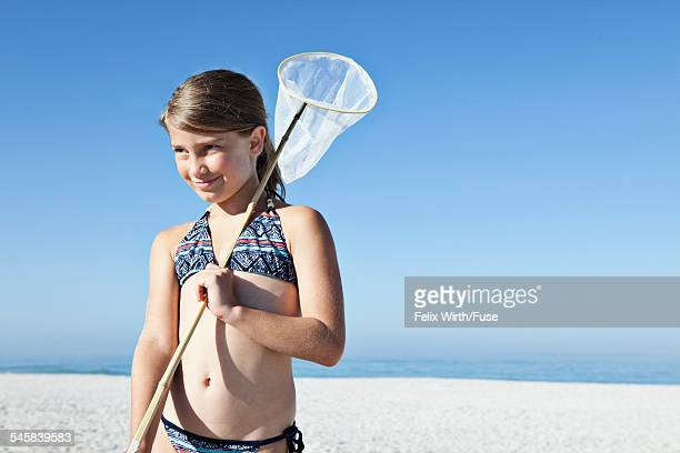Girl (10-12) holding fishing net and looking away