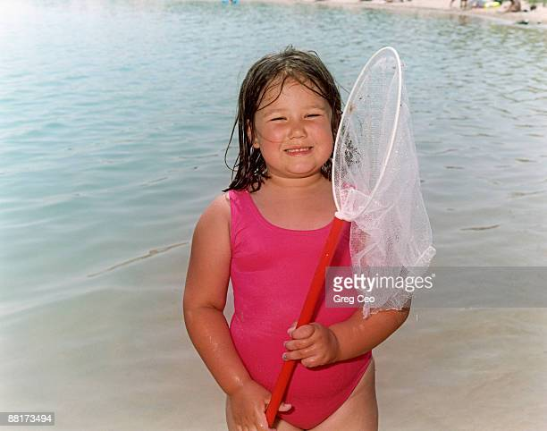 Girl holding fishing net by lake