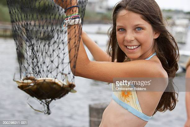 Girl (10-12) holding fishing net containing crab, close-up, portrait