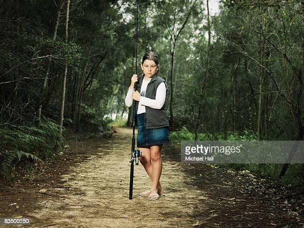 Girl holding fishing rod on bush track