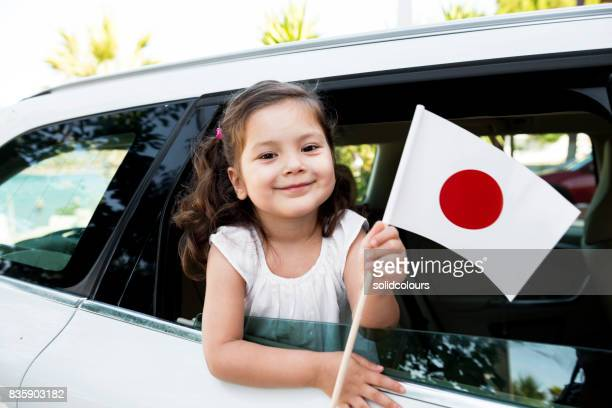 girl holding flag of japan - japanese flag stock photos and pictures