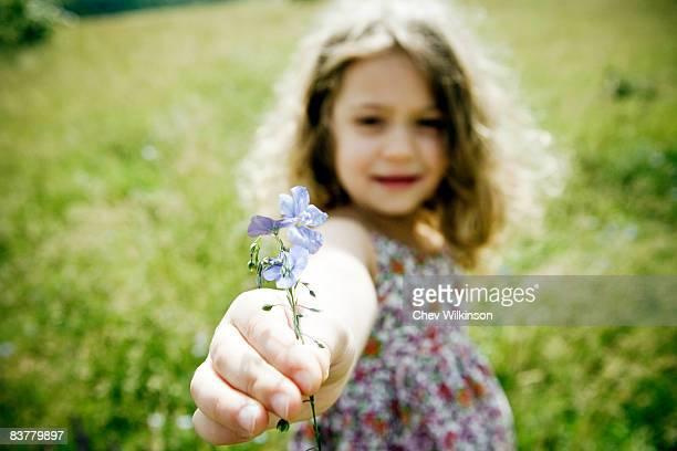 Girl holding flower to camera